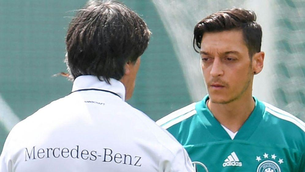 Mesut Özil (r.) will sich mit Joachim Löw (l.) versöhnen - Bildquelle: AFPSIDPATRIK STOLLARZ