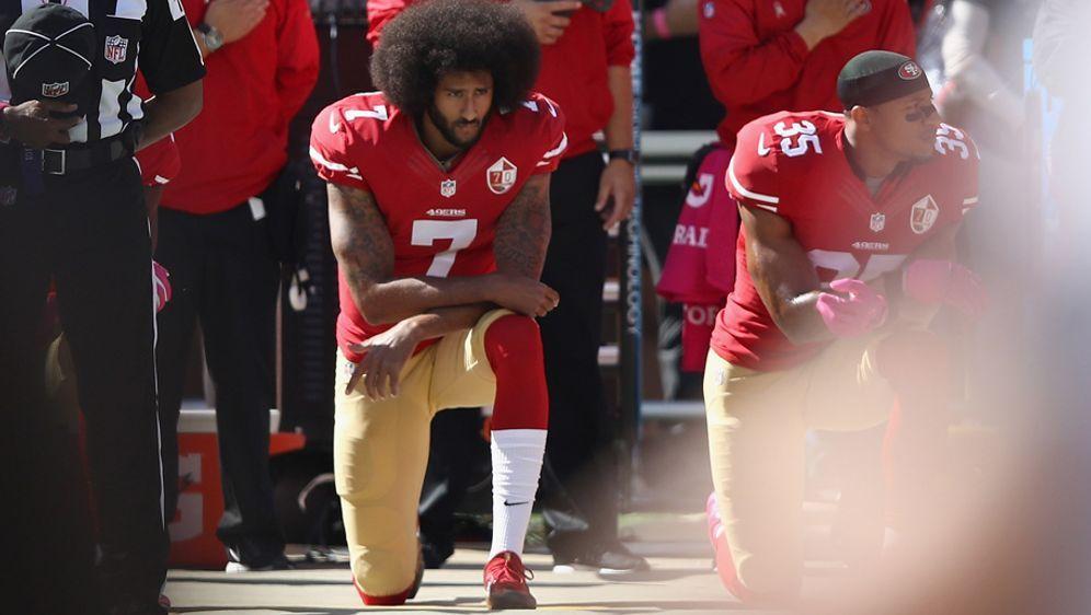 Colin Kaepernick (li.) kniet während der US-Hymne - Bildquelle: 2016 Getty Images