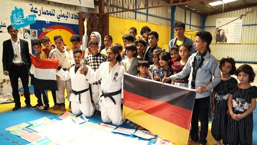 Nashwan mit Fackel und Deutschland-Fahne in der Hand - Bildquelle: SugarJudoSugarJudo@JudoNashwanMohammed Nashwan